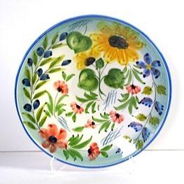 Ett runt stort fat 42 cm med underbara blommor handmålade. Svensk design av konstnär Lena Linderholm och producerad i Portugal. Blommorna utgöres av röda vallmo, solrosor och blåblommor med inslag av svarta oliver på kvist samt gröna blad. Helt underbart i sin egen form men kan användas till uppläggning av mat på. Tål maskindisk.
