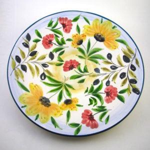 Handmålat stort runt fat 41 cm. Blommorna utgöres av vallmo, solrosor och svarta oliver på kvist. Fatet är något skålat och kan användas till mat, frukt sallader men är fantastisk vacker och gör sig som en mycket vacker dekoration. Färgen runt fatet är målat i petrol grön och allt är målat för hand. Designen är gjord av Lena Linderholm. Produktionen sker i Portugal