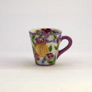 En vacker blommig konformad keramik mugg med viol blommor. Lila kant uppe runt öppning på muggen och örat, handtaget i lila och vit. En violblomma inuti muggen. Keramiken är handmålat efter Lena Linderholms akvareller och design. Producerad i Portugal. Muggen rymmer 4 dl vätska. Höjd 10 cm. Öppningen är 10 cm. Botten 6 cm. Muggen tål maskindisk och microugn.