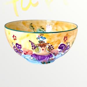 En unikt handmålad skål från Lena Linderholms kollektion Happy girl. Skålen går i toner av ockragult, dimblå. Målningar på skålen och runtomkring i form av en flicka med en fågel på huvudet, olivkvistar, blommor, fjärilar. Allt i välavstämda färger.