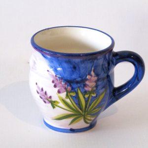 En rund och bullig härlig mugg med öra i fajans keramik. Färgerna skiftar från blått, lila och ljusare lila rosa. Lavendel kvistar sprakar på i lila och gröna färger på muggen. Hela muggen är målad för hand och designen är konstnärinnan Lena Linderholm. Inspiration hämtad från lavendelfärgen i Provence.
