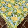 Vacker duk i vaxtyg med härligt solgula citroner med gröna blad. Bakgrundsfärgen är ljusblå som en himmel med lite gröna inslag. Svensk design av konstnärinnan LeNA Linderholm.