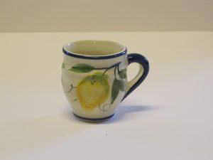En mjuk bullig mugg i begie/vit bottenfärg med gula citroner i olika gula nyanser och med ett grönt bladverk med olika gröna nyanser. Koppen har öra i marinblått. Kanten upptill har också en en mariblå rand.